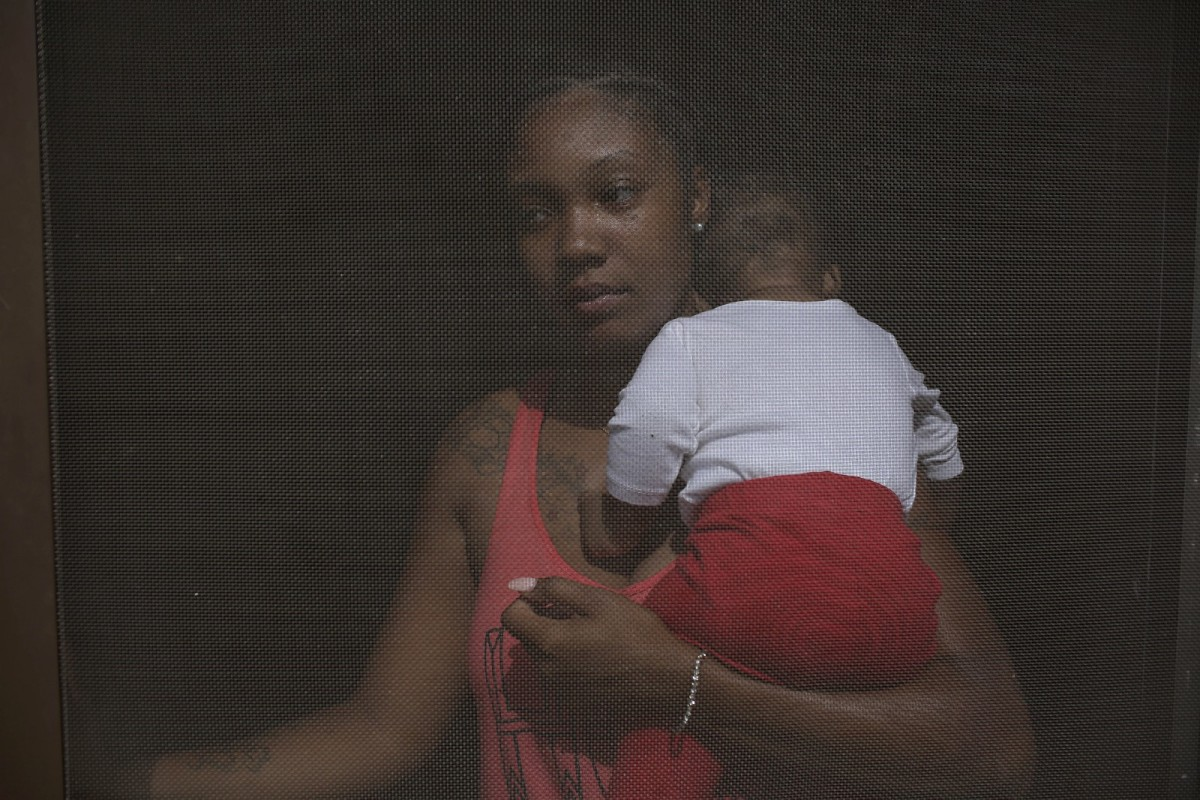 Kamia Edwards holds her son Darrell Jackson inside her apartment at the West Calumet Housing Complex in East Chicago, Indiana.