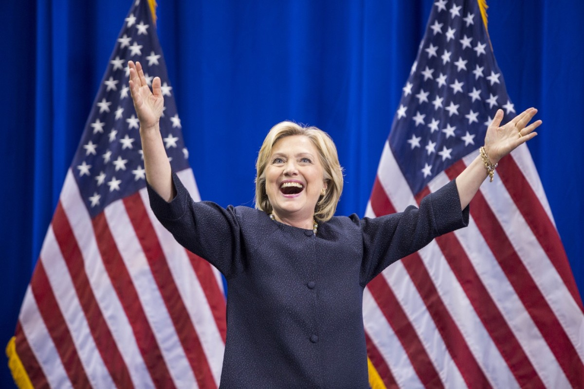Photo of Hillary Clinton in front of American flags, with her arms upraised