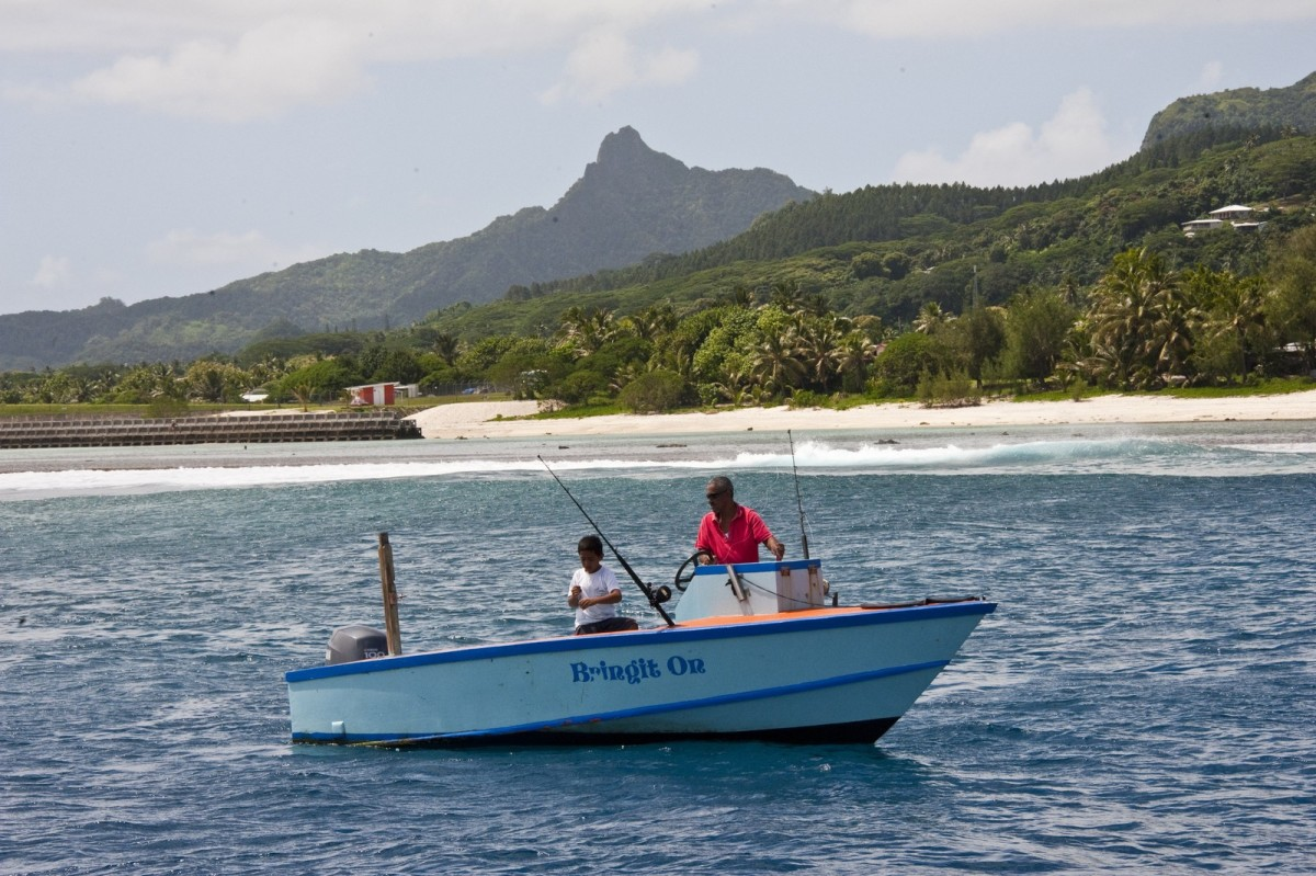 Photo showing two people fishing in a small motorboat just offshore of a tropical island