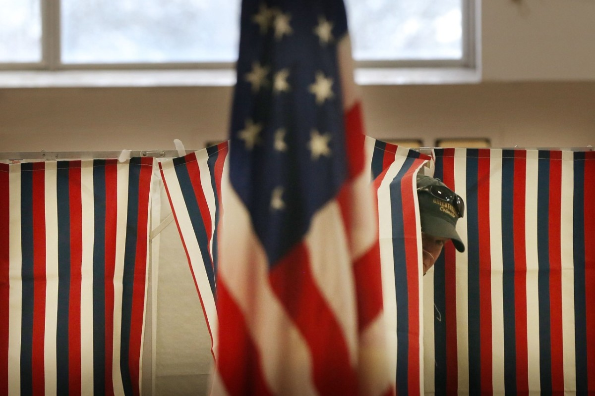 A man exits a voting booth inside of a middle school serving as a voting station.