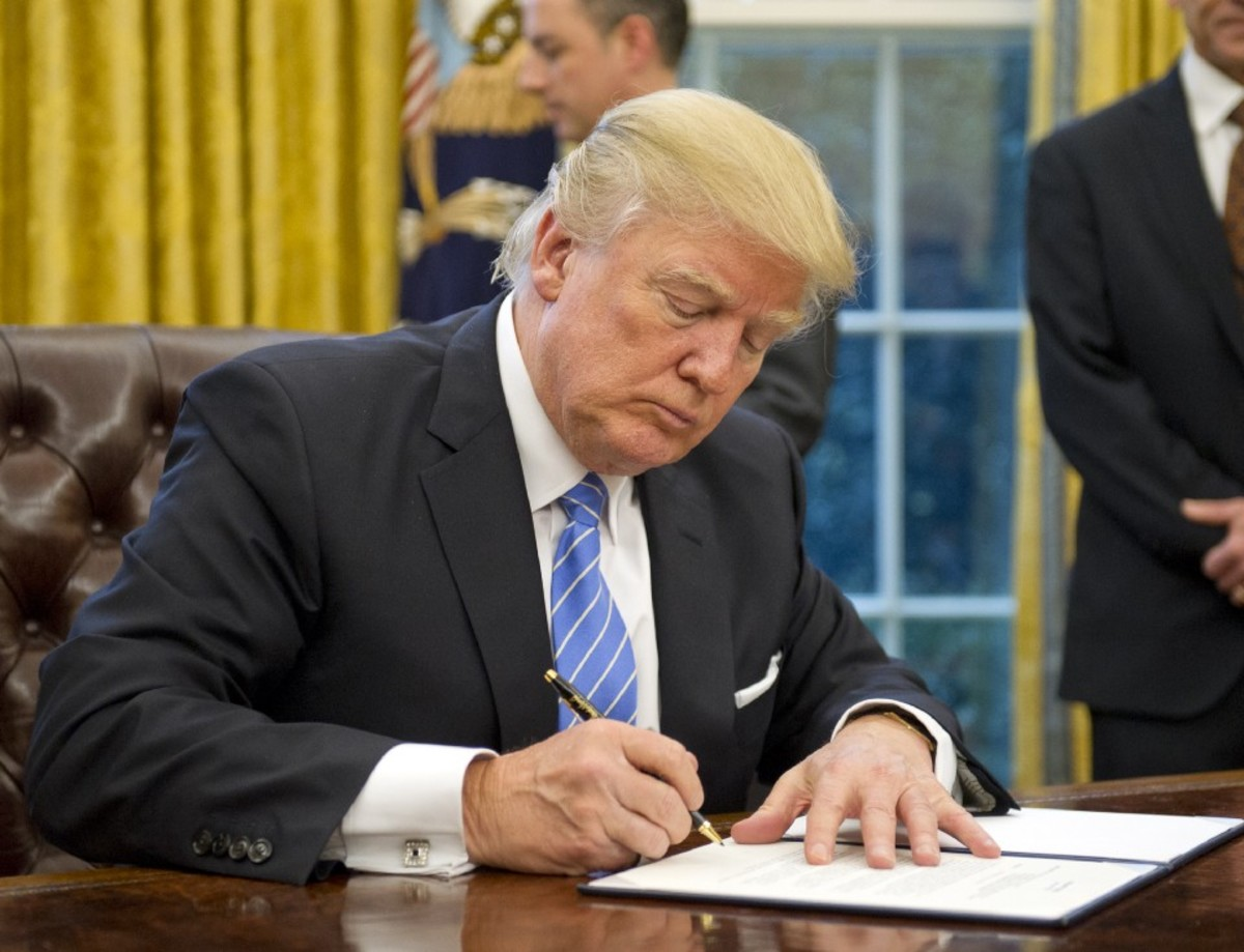 Photo showing President Donald Trump signing executive orders at his desk