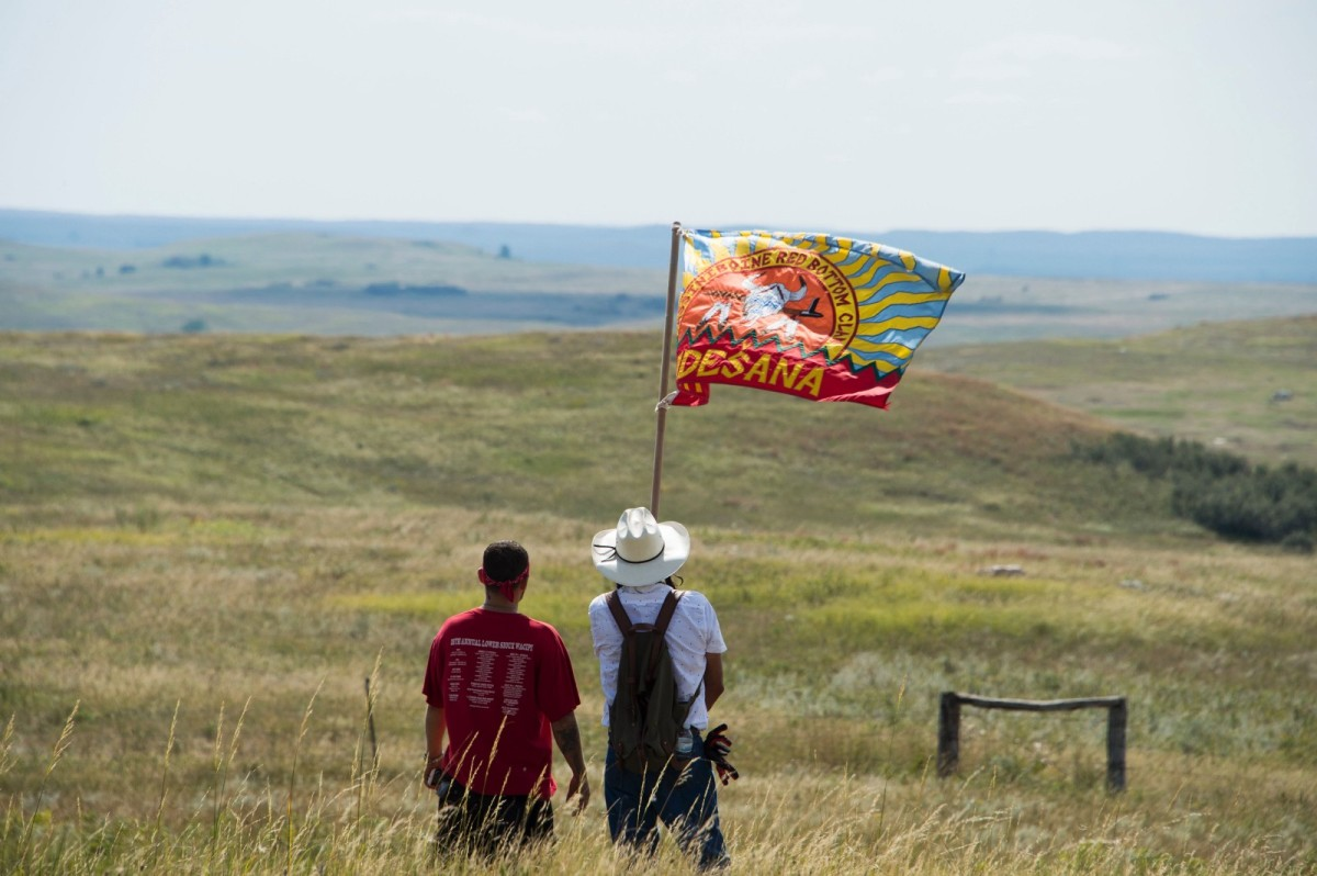 Native American protestors wave a flag over land designated for the Dakota Access Pipeline on September 3rd, 2016, near Cannon Ball, North Dakota.