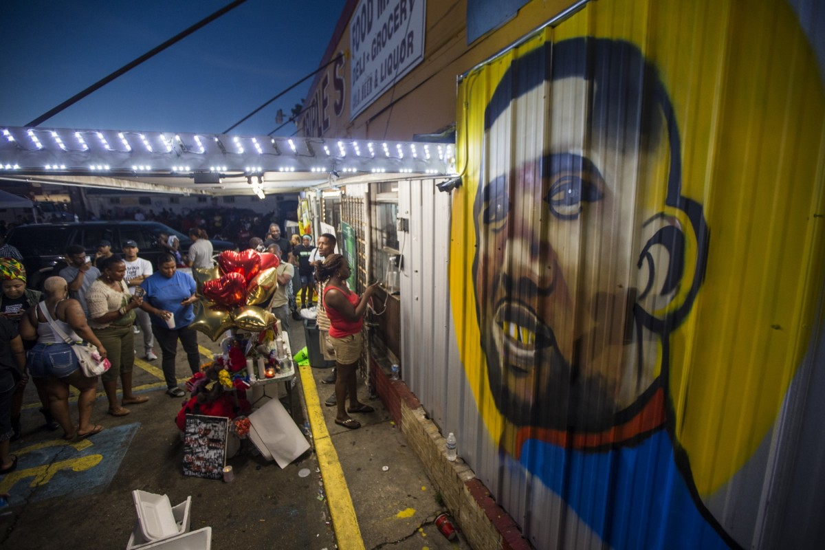 Mourners gather in front of a mural painted on the wall of the convenience store where Alton Sterling was shot and killed in Baton Rouge, Louisiana.