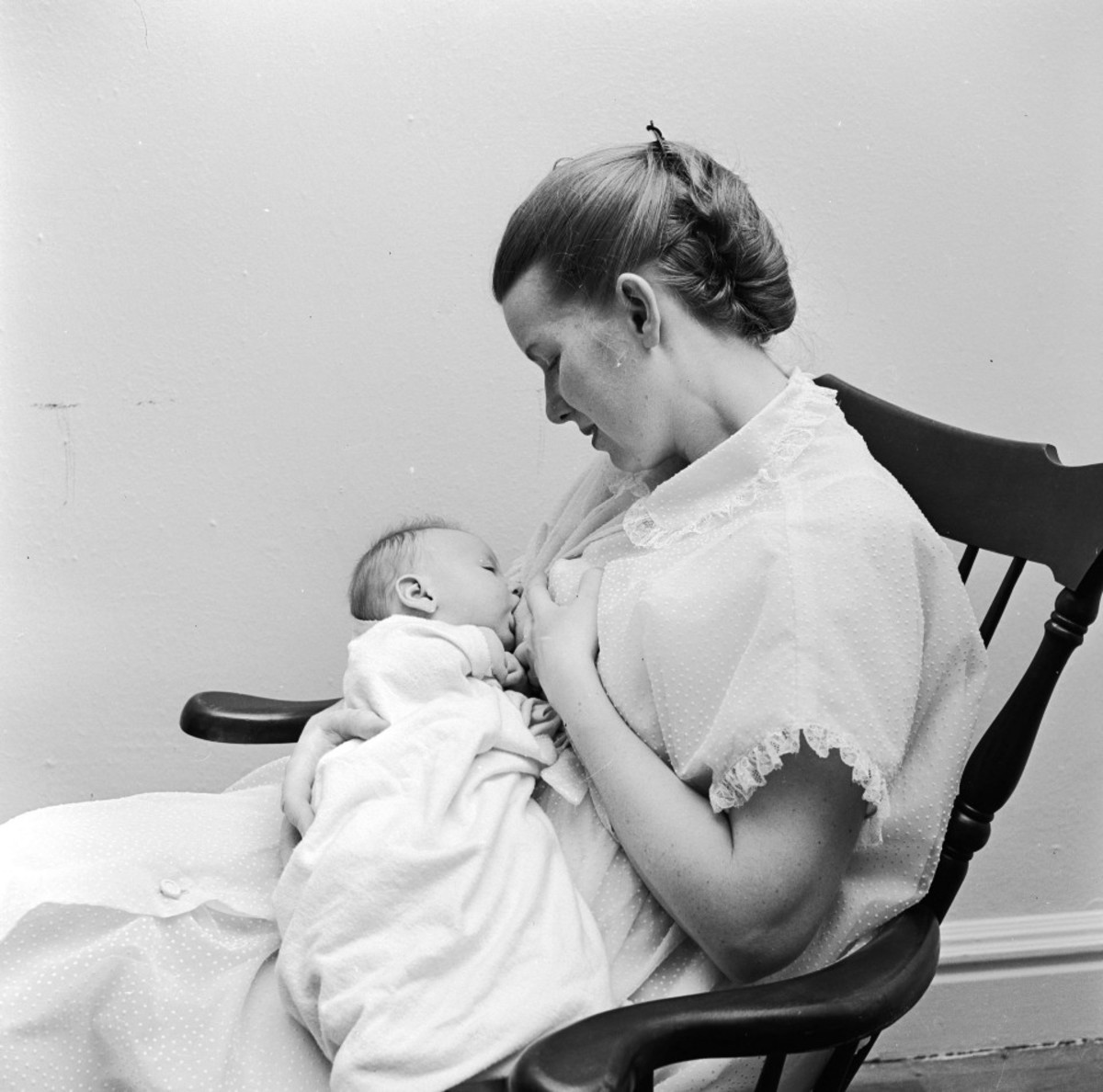 Black-and-white photo showing a woman in a rocking chair, breastfeeding an infant