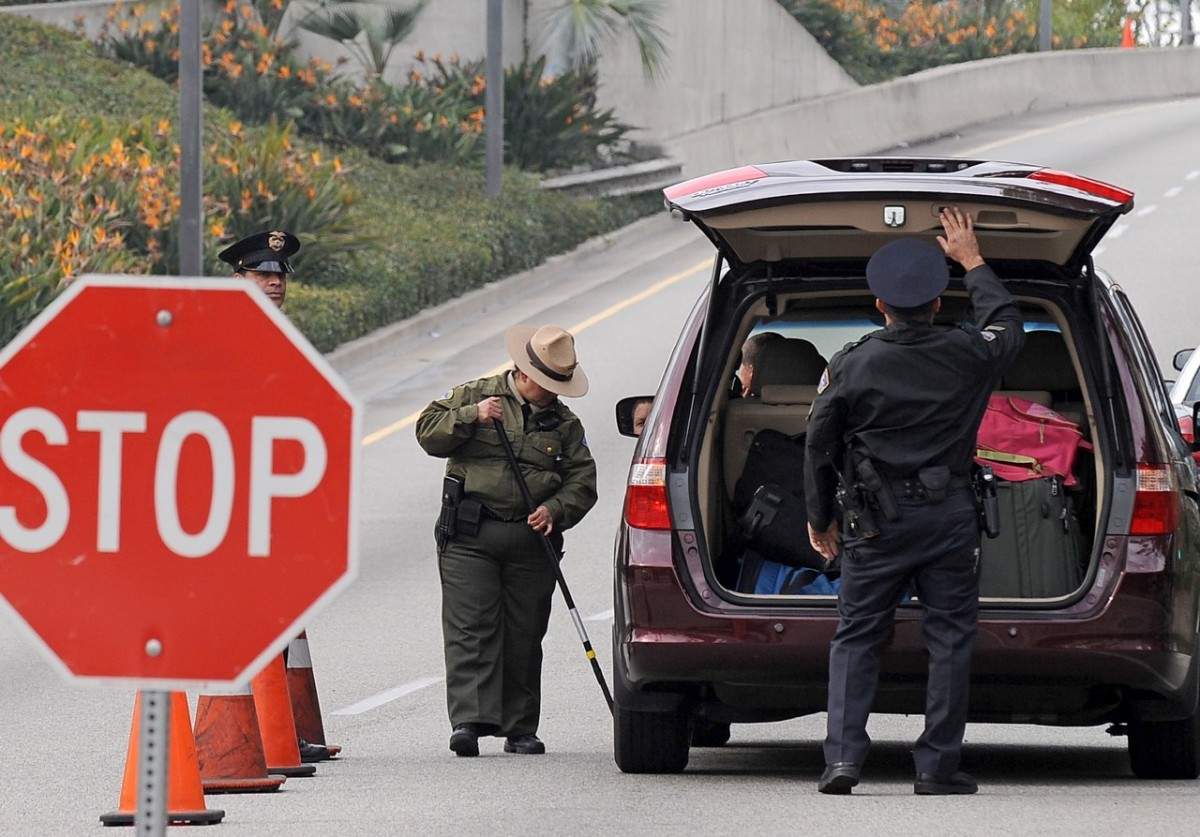 Police officers search a car at Los Angeles International Airport. (Photo: Robyn Beck/AFP/Getty Images)