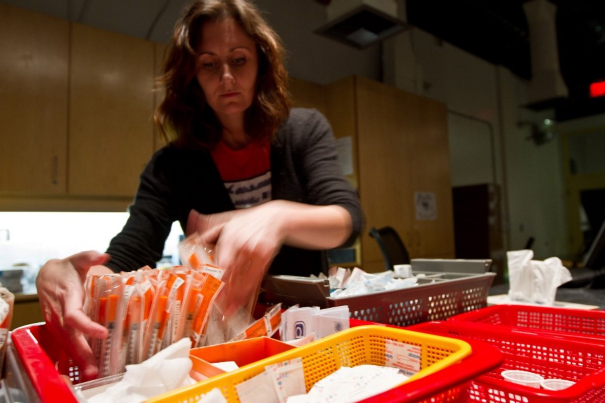 An Insite employee arranges syringes.