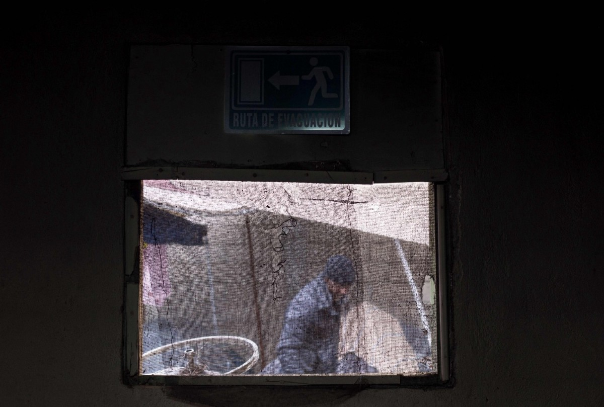 A Haitian migrant seeking asylum in the United States is seen through a window in Tijuana, Mexico.