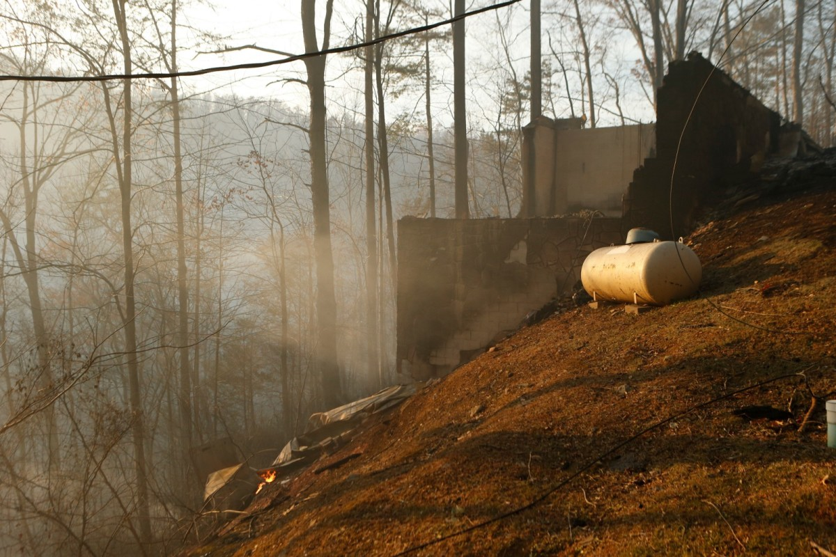 The remains of a home smolders after a wildfire November 29th, 2016, in Gatlinburg, Tennessee.