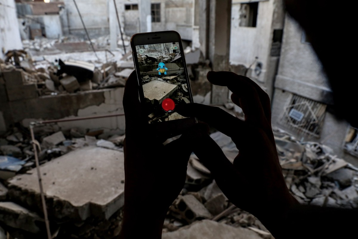 A Syrian gamer uses the Pokemon Go application on his mobile to catch a Pokemon amid the rubble in the besieged rebel-controlled town of Douma, a flashpoint east of the capital Damascus on July 23rd, 2016.