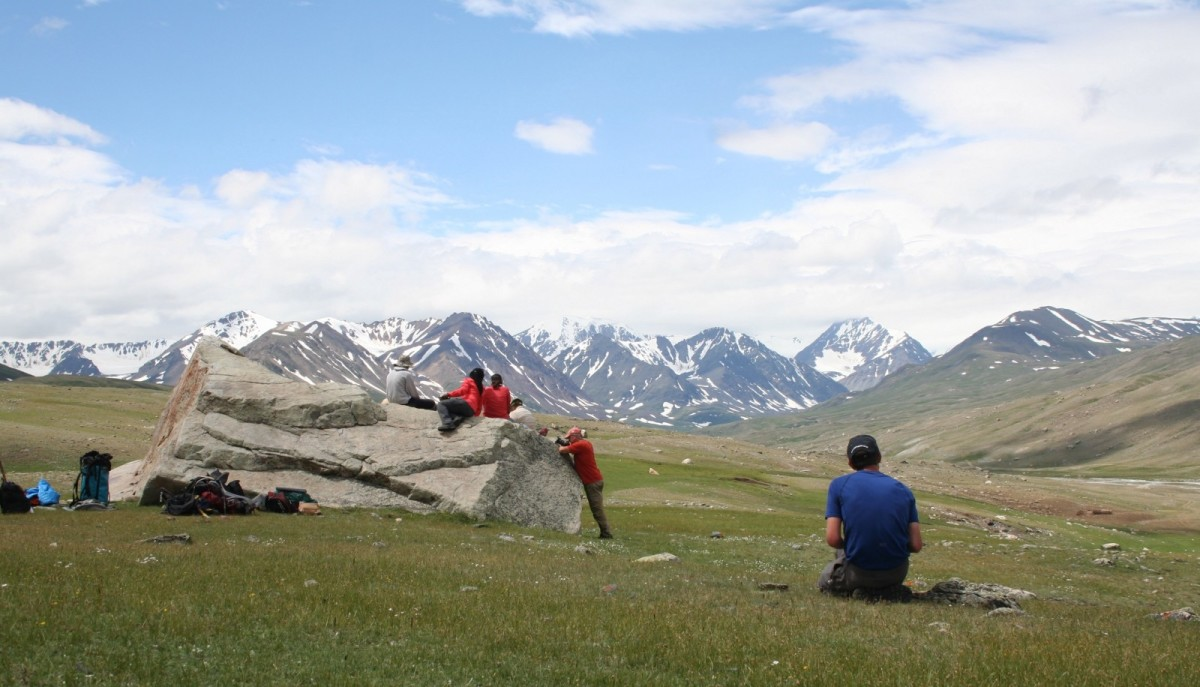 The field team atop the first rock sample of the expedition. Foreground: Aaron Putnam sketches in his notebook.