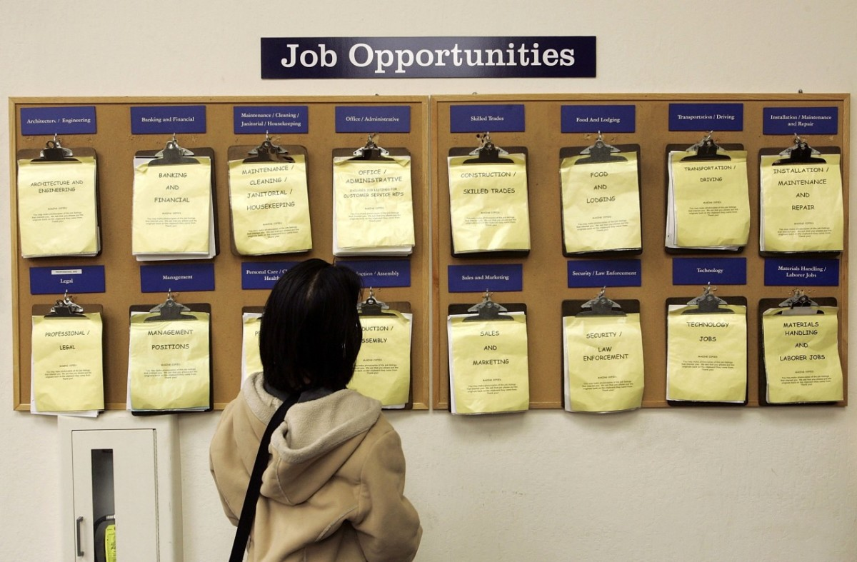 A woman looks at a job listing board at the East Bay Career Center in Oakland, California.