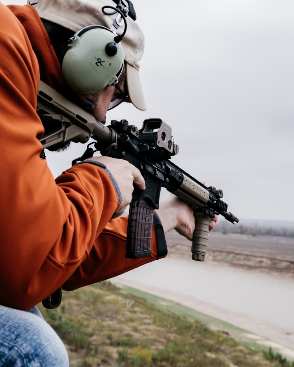 A gunner looks down the red dot sight of an AR-15 over field and river while searching for feral hogs. (Photo: Benjamin Rasmussen)