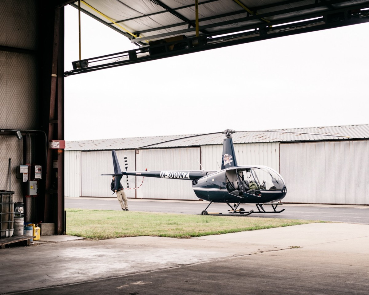 Helibacon's Robinson R44 Raven II helicopter is rolled out of its hanger for a morning flight. (Photo: Benjamin Rasmussen)