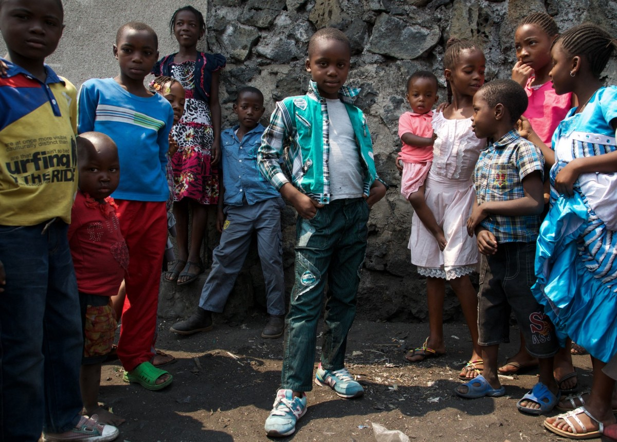 A young boy poses with a group of friends, taking a break from practicing his dance moves to show off his coordinated outfit. People under 25 make up 63.64 percent of the DRC's population.