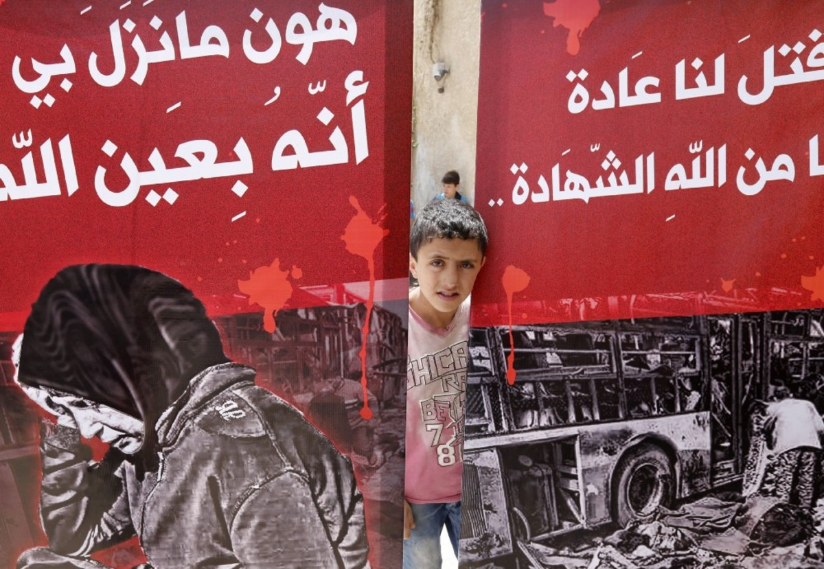 A child looks out from behind posters during a funeral ceremony in Damascus, Syria, on April 26th, 2017, held for the victims of a bombing that targeted buses carrying evacuees. (Photo: Louai Beshara/AFP/Getty Images)