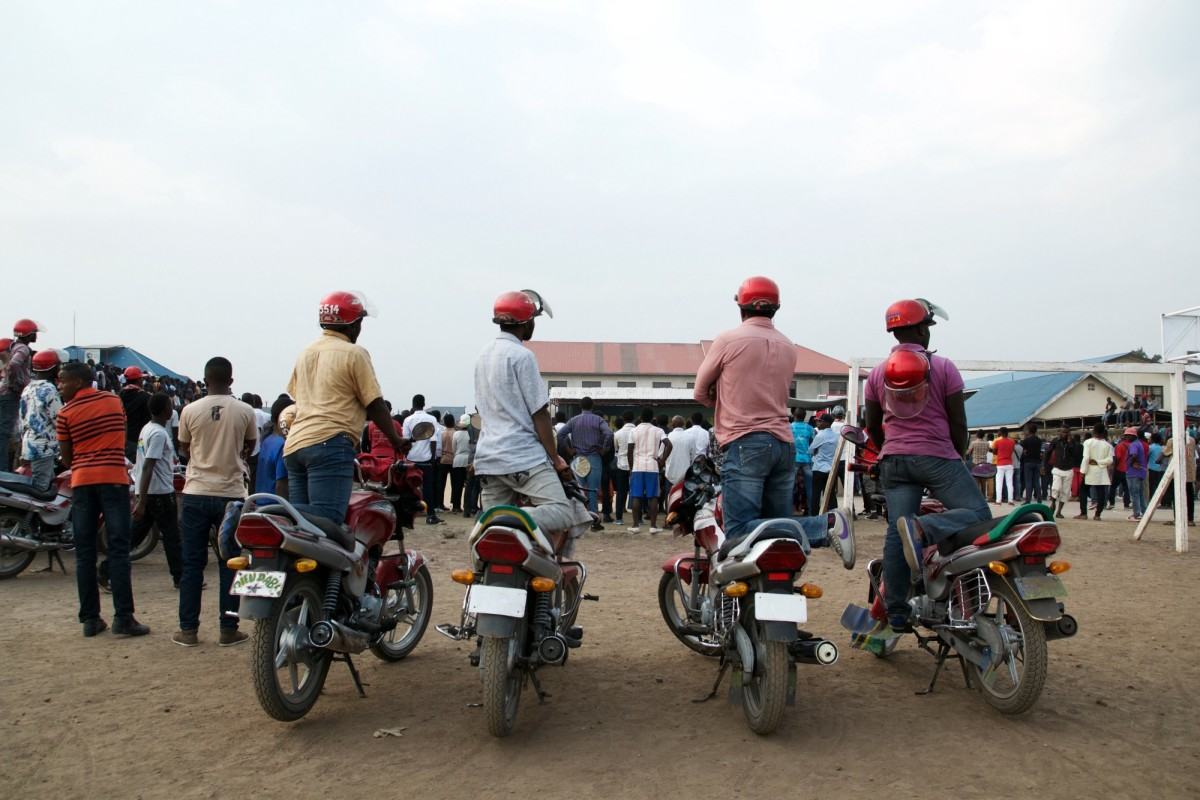 "Four motorcycle taxis watch a concert at Sanaa Weekend—""sanaa"" is the Swahili word for art—at the Goma Cultural Center. On Saturdays, around 4,000 people arrive at the center to see free, live performances. Started in 2012, the event is an opportunity for the dancers to perform their skills in front of a live audience."