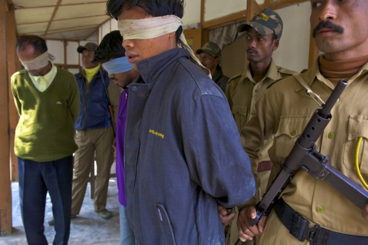 Men apprehended by park guards as suspected rhino poachers. (Photo: Steve Winter/National Geographic Creative/Mongabay)
