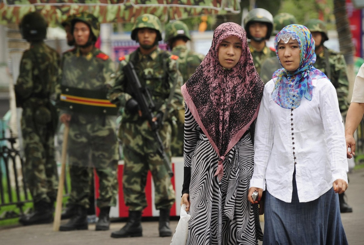 Two ethnic Uyghur women pass Chinese paramilitary policemen.