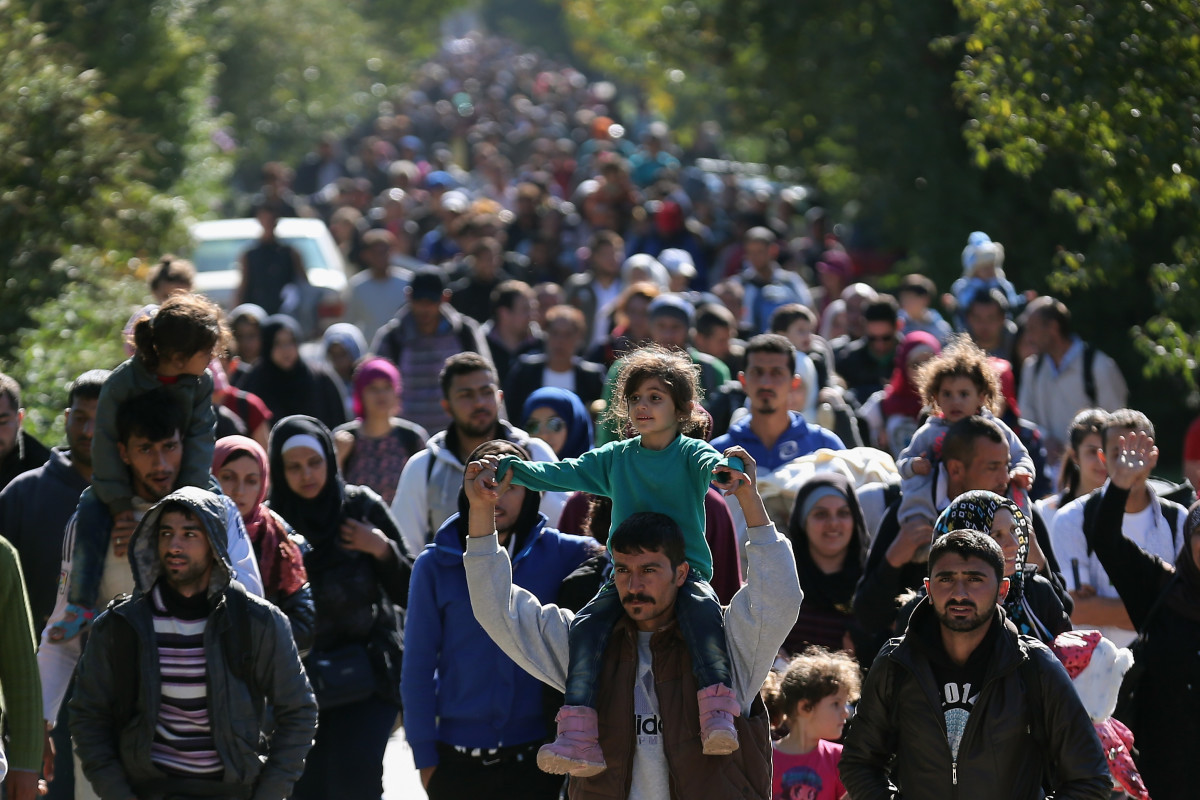 Hundreds of migrants who arrived by train at Hegyeshalom on the Hungarian and Austrian border walk the four kilometers into Austria on September 22nd, 2015, in Hegyeshalom, Hungary.