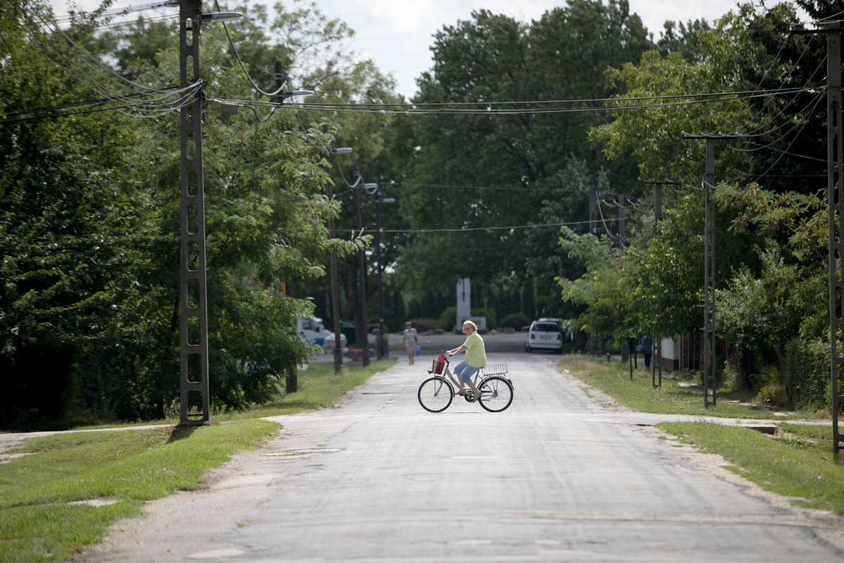 A woman rides her bike along an empty road close to the railway station in Hegyeshalom, Hungary.