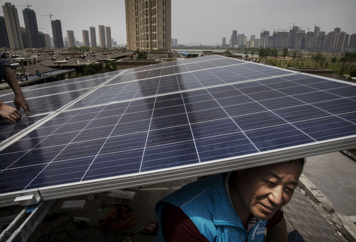 Chinese workers from the Wuhan Guangsheng Photovoltaic Company install solar panels on the roof of a building in Wuhan, China, on April 27th, 2017.