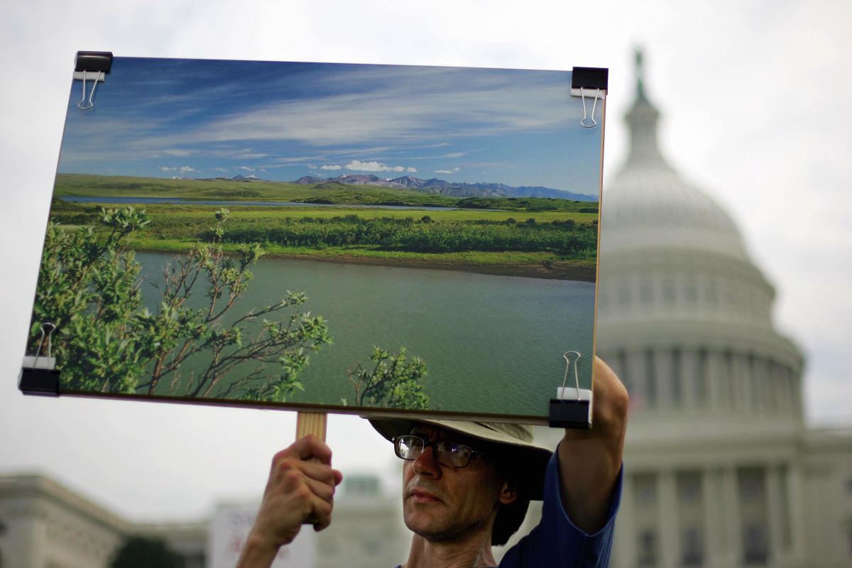Thomas Joswiak holds a photograph of the Arctic National Wildlife Refuge at a large rally on the West Lawn of the Capitol.