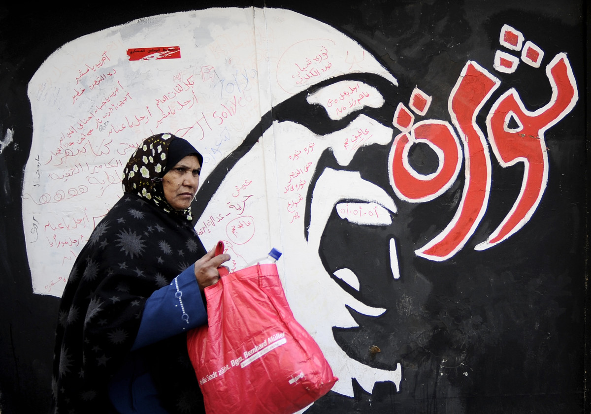 An Egyptian woman walks past graffiti near Tahrir Square in Cairo, Egypt, on December 21st, 2011.