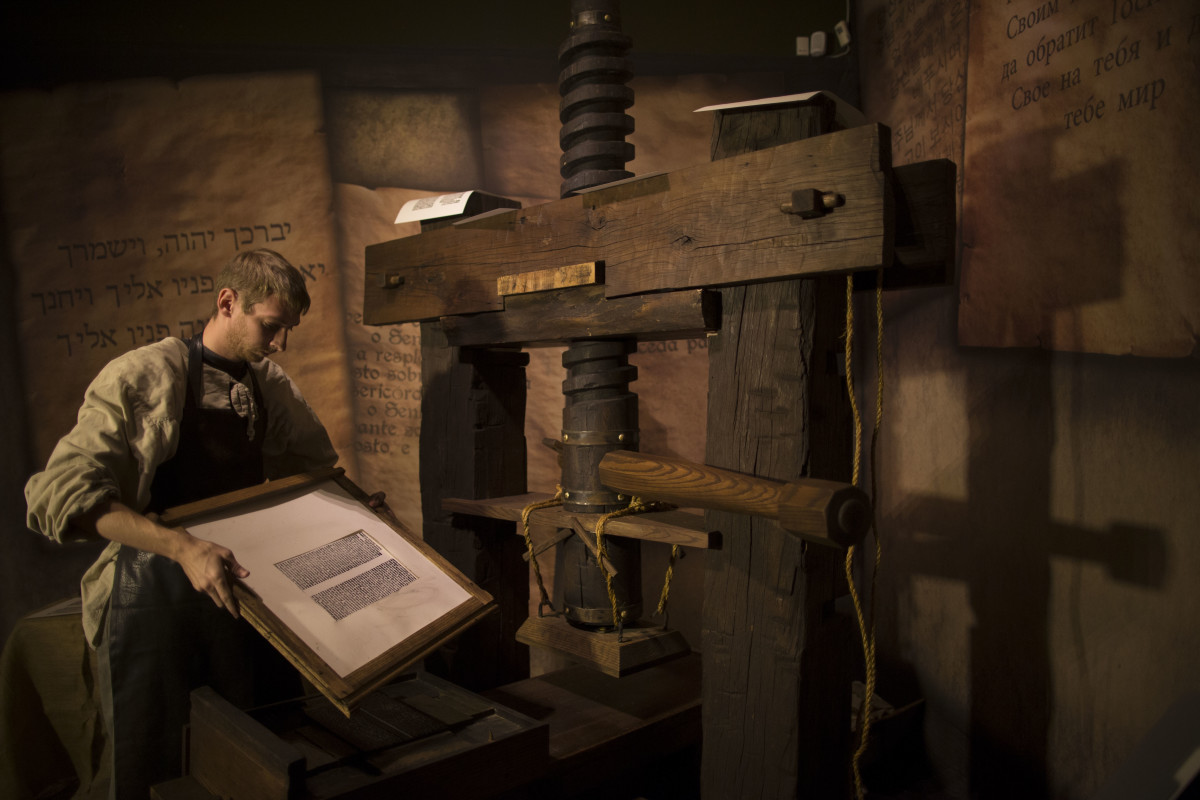 A museum employee shows how a Johannes Gutenberg replica printing press is used at the Book of Books exhibition in the Bible Lands Museum on October 23rd, 2013, in Jerusalem, Israel.