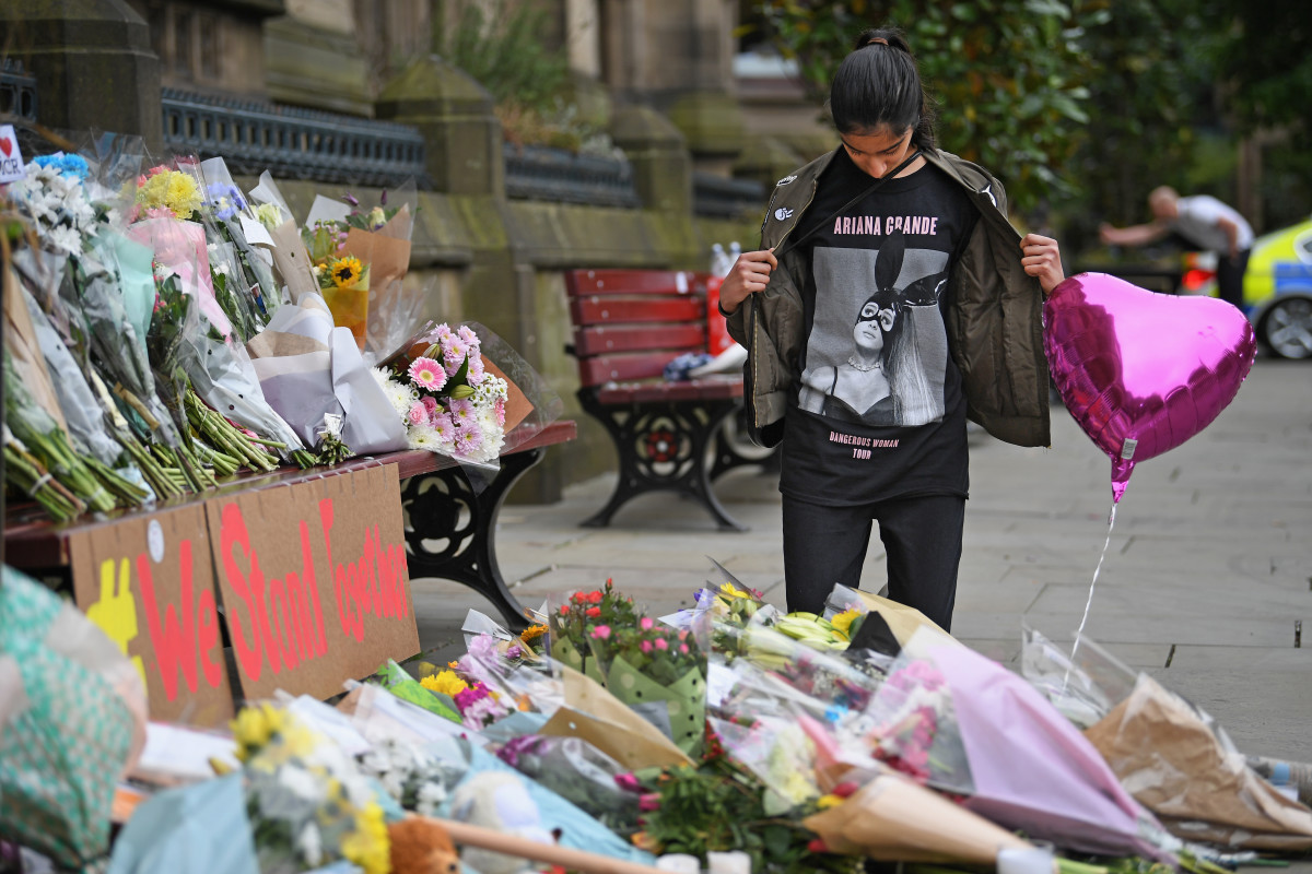 A 13-year-old girl who attended the Ariana Grande concert looks at floral tributes and messages in Manchester, England, on May 24th, 2017.
