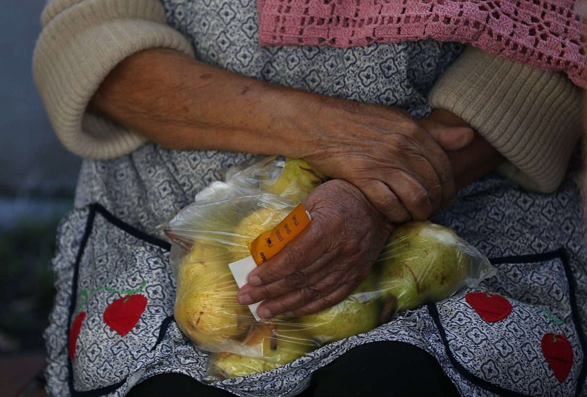 A woman holds a bag of pears.