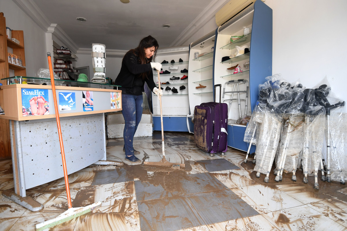 A Tunisian woman cleans her orthopedic shop in Manouba on June 6th, 2017, following a storm the previous night.
