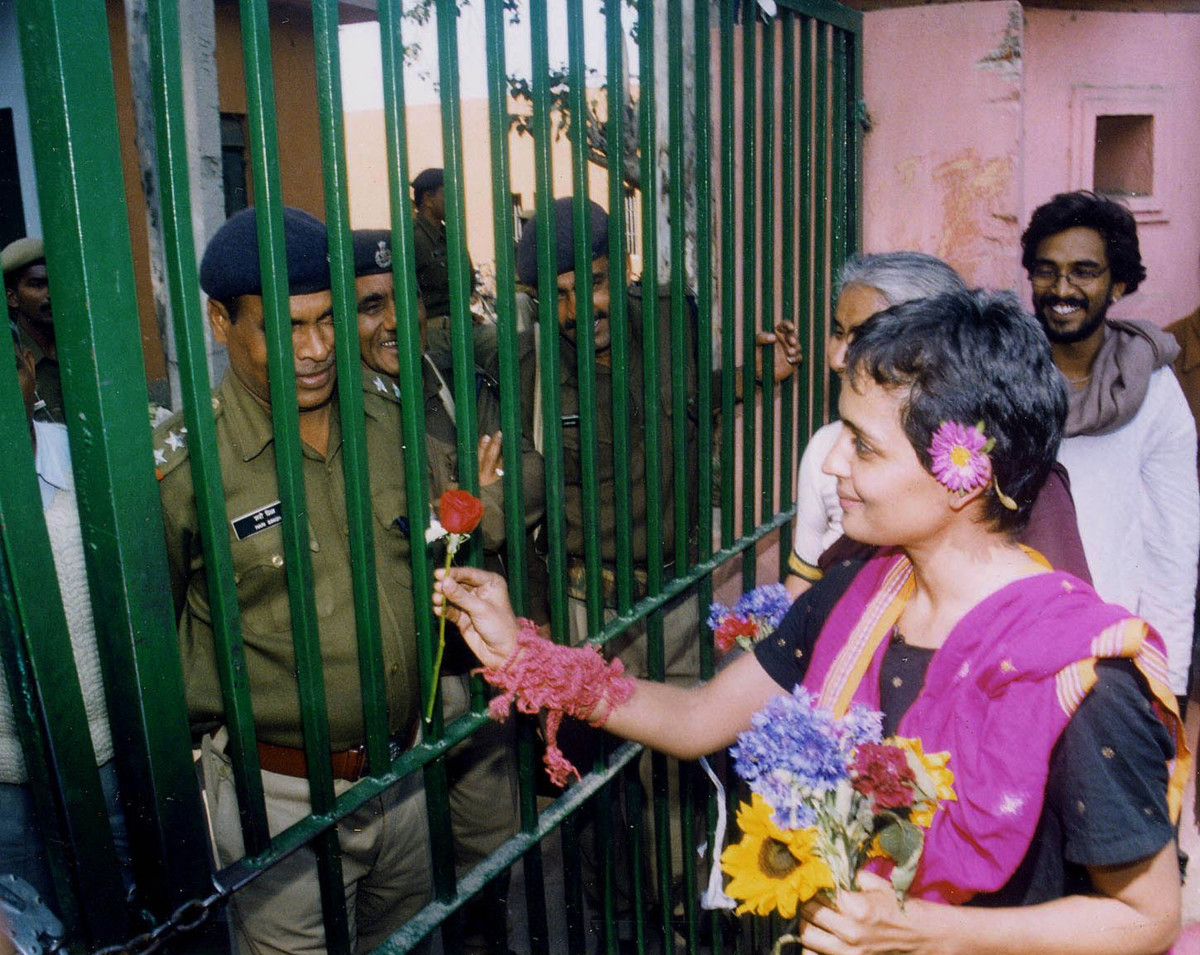 Arundhati Roy presents a flower to the jail guards as she leaves the Tihar Central Jail after serving a short sentence for contempt of court in New Delhi, India, on March 7th, 2002.