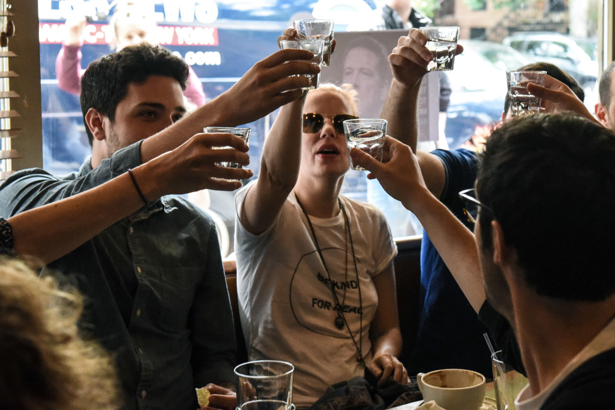 People drink while watching former FBI Director James Comey's testimony on June 8th, 2017, in Brooklyn, New York City.