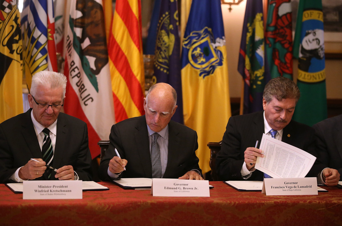 Winfried Kretschmann, minister-president of the German state of Baden-Wurttemberg, California Governor Jerry Brown, and Baja California Governor Francisco A. Vega de Lamadrid sign a climate change bill during at the Leland Stanford Mansion in Sacramento, California on May 19th, 2015.
