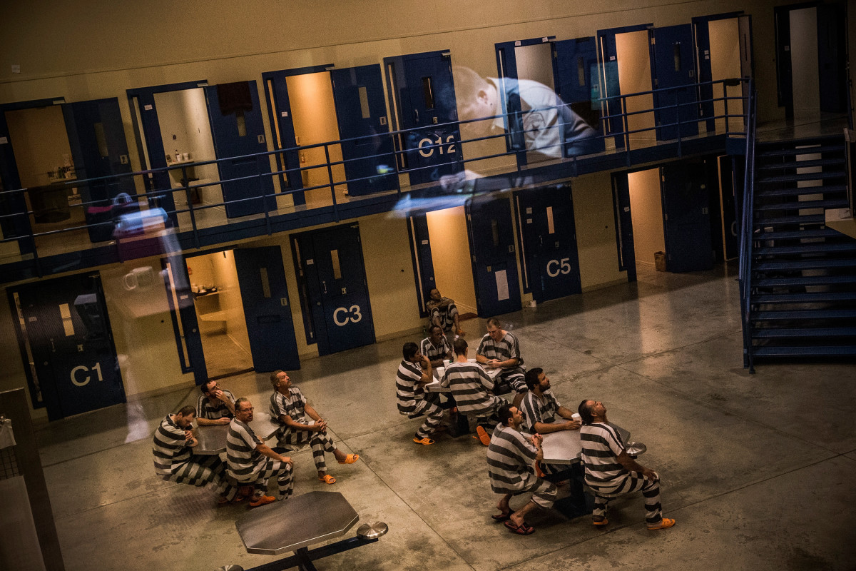 An officer is reflected in the glass as inmates sit in the county jail on July 26th, 2013, in Williston, North Dakota.