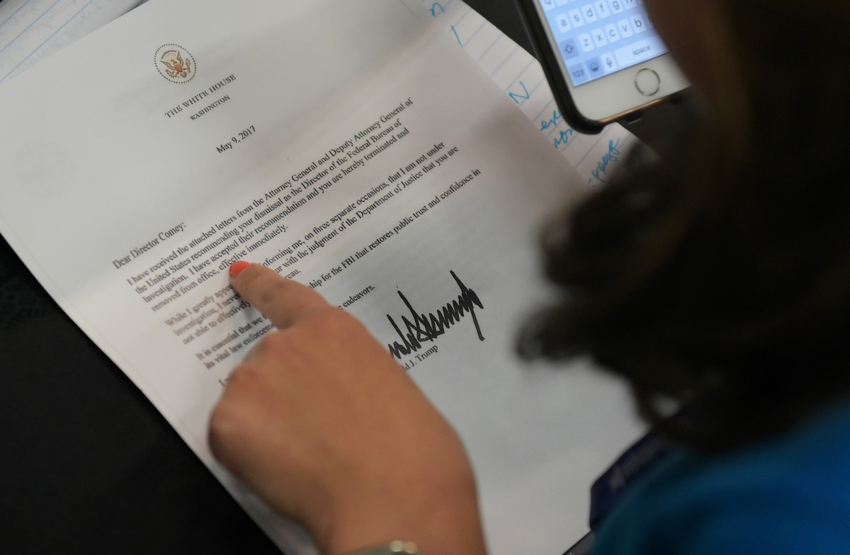A journalist looks at a copy of the termination letter to Federal Bureau of Investigation Director James Comey from President Donald Trump.