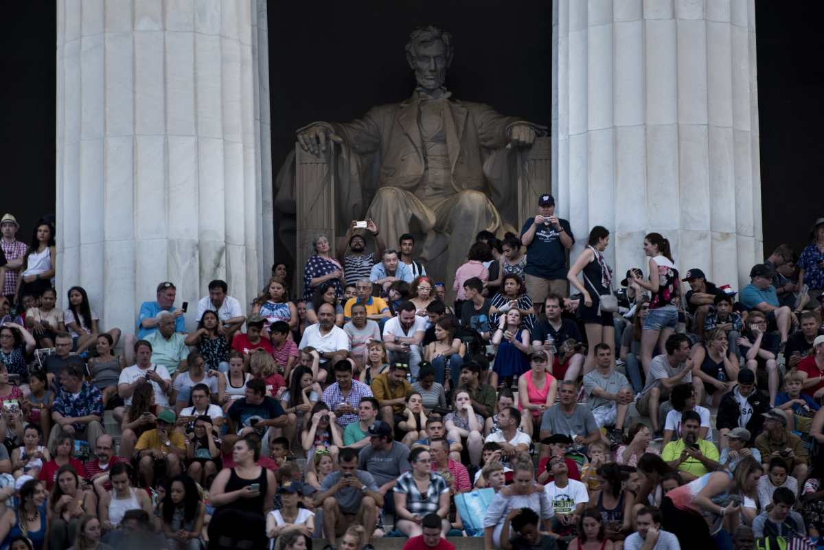 People wait on the Lincoln Memorial for fireworks to celebrate Independence Day on July 4th, 2017, in Washington, D.C.