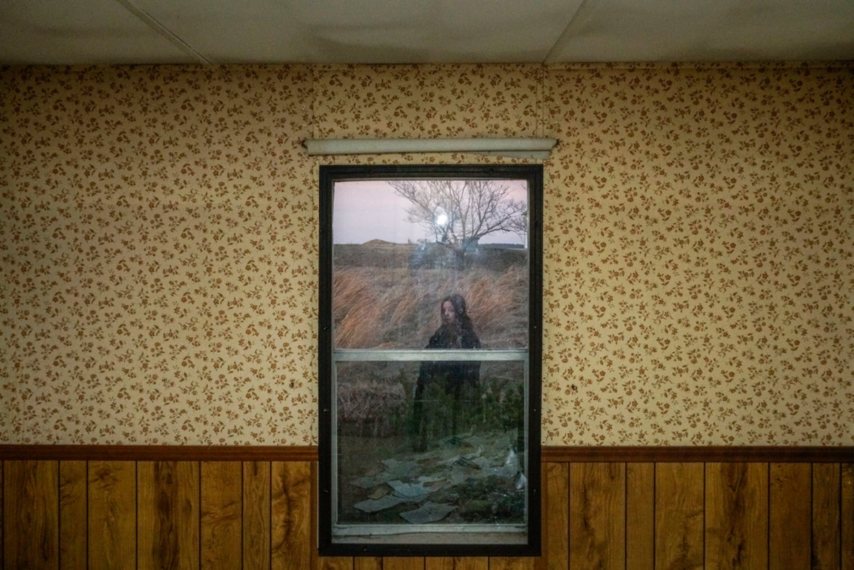 Georgia de la Garza, a local environmental activist in southern Illinois. She is pictured from inside an abandoned house near the Eagle River Coal Mines.