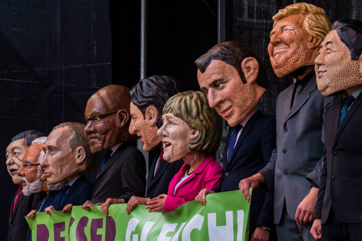 "Performers wearing masks of world leaders hold a placard reading ""Better Off Equal! Close the Gap Between Rich and Poor"" during a demonstration called by several non-governmental organizations ahead of the G20 summit in Hamburg on July 2nd, 2017."