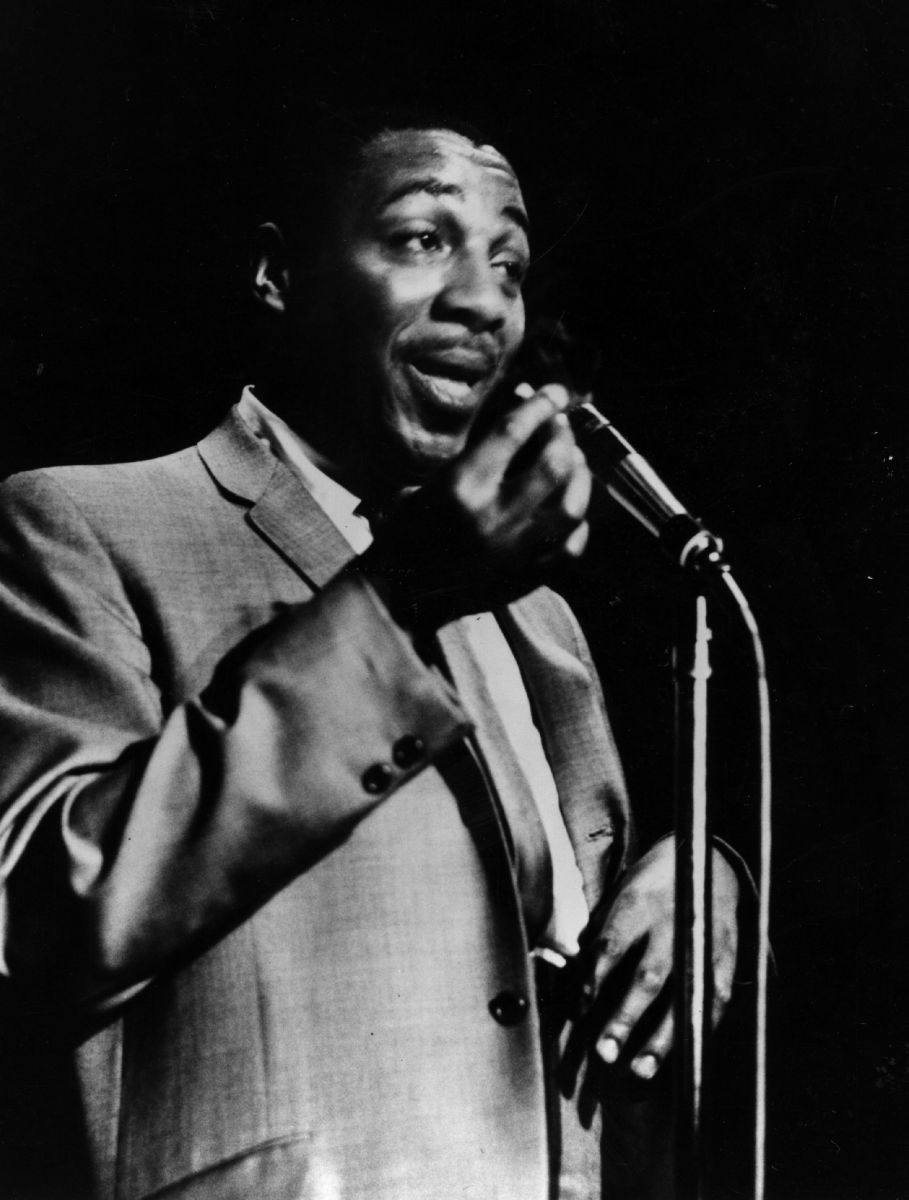 Dick Gregory at the microphone in 1962.