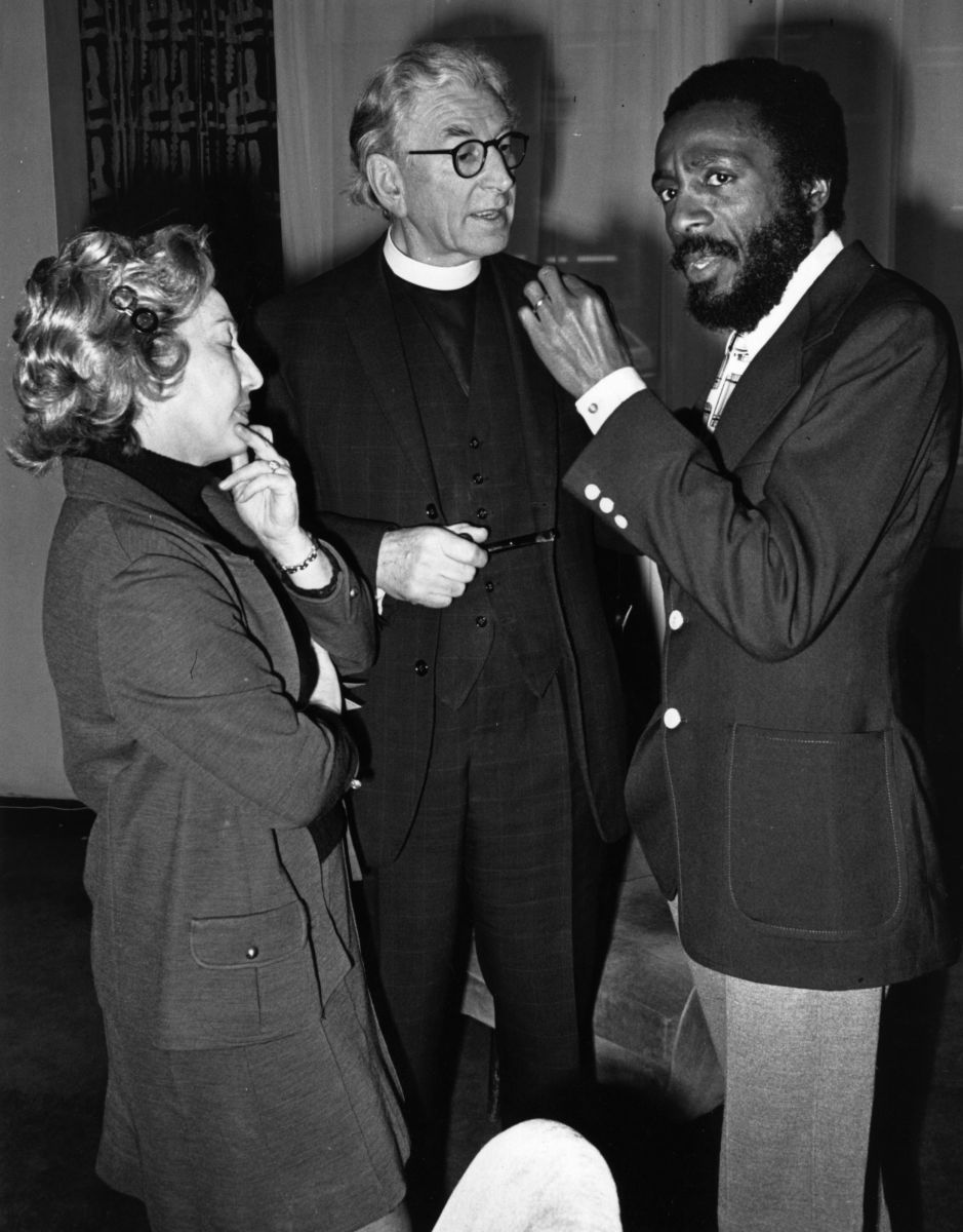 Dick Gregory talks to Canon Collins (center) at St. Paul's Cathedral the week before giving a show during a special celebration for the International Year Against Racial Discrimination in December of 1971.