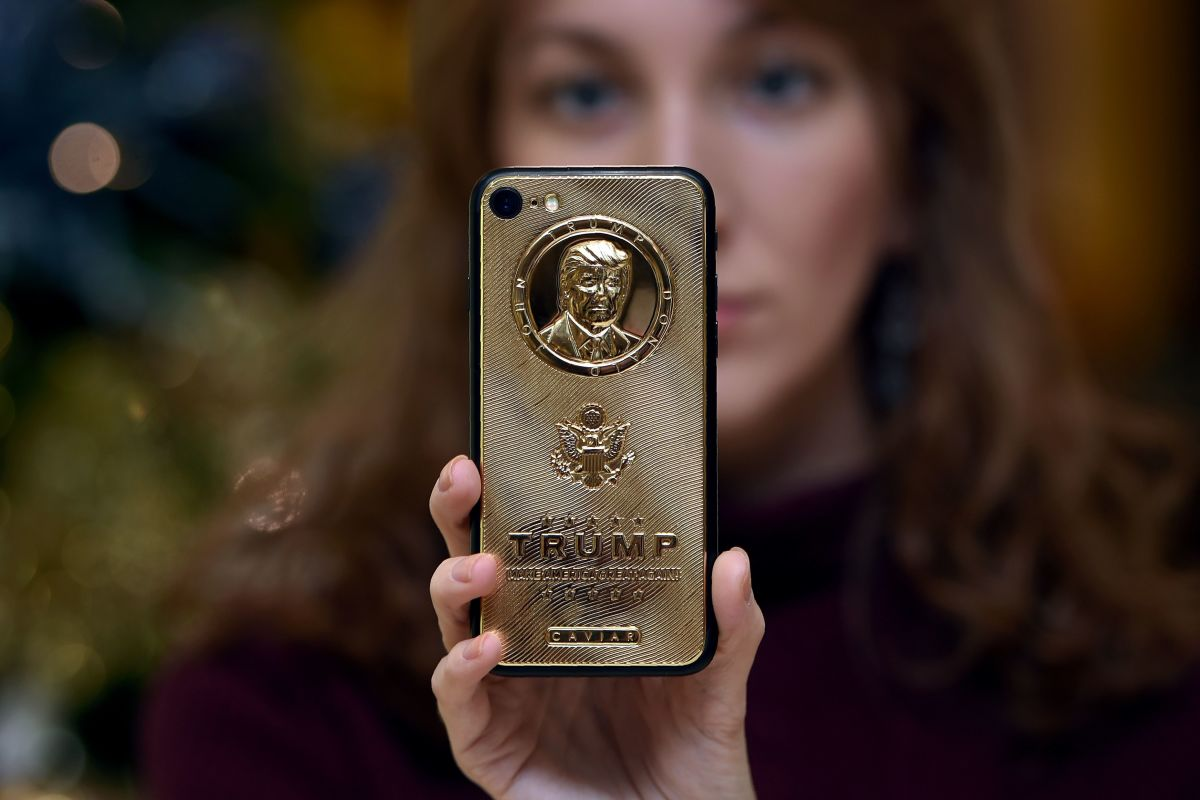An employee of Caviar Phones, a Russian-Italian company specializing in smartphone customization, displays a special gold-plated iPhone 7 smartphone bearing the likeness of President Donald Trump.