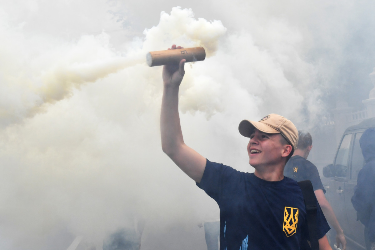An activist holds up a flare during a protest in front of Ukrainian Parliament in Kiev on July 11th, 2017, demanding the removal of immunity for deputies. The parliament of Ukraine is debating the submission by the general prosecutor's office on the removal of parliamentary immunity from five parliamentarians suspected of corruption.