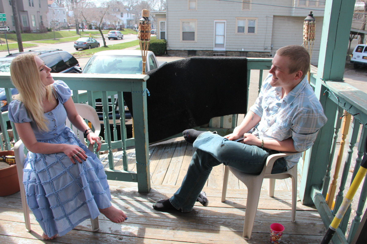 Chanda Lynn Germain and Zack Dahlbeck sit talking on their porch at home in Jamestown, New York.