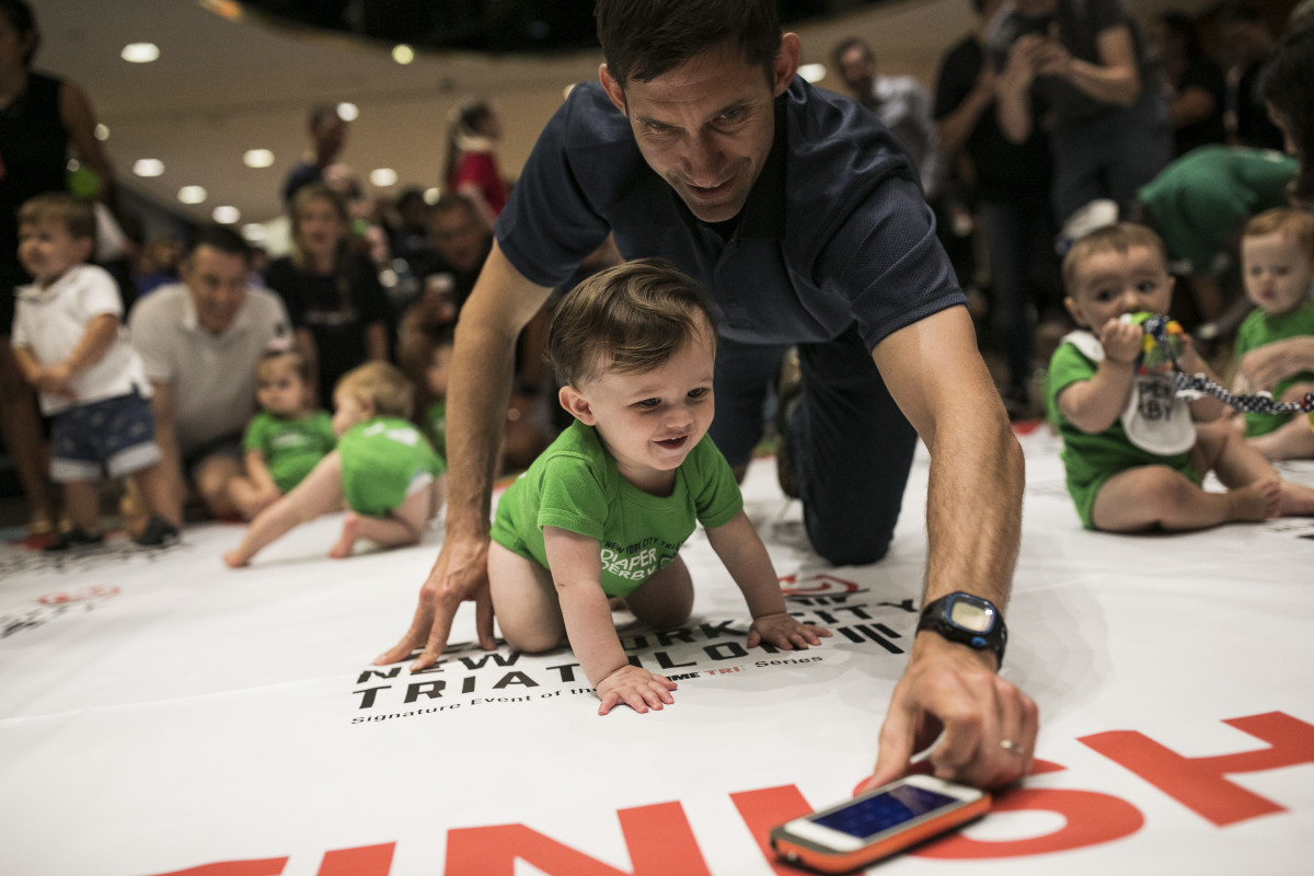 A father lures his child along with an iPhone during warm-ups before babies race in the NYC Triathlon's annual Diaper Derby on July 14th, 2017, in New York City.