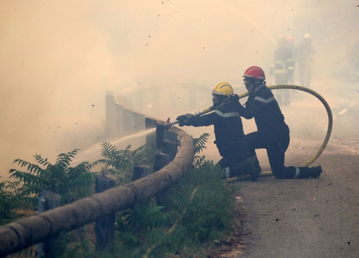 Firefighters use a hose to spray water as they fight against a fire in Castagniers, France, on July 17th, 2017.