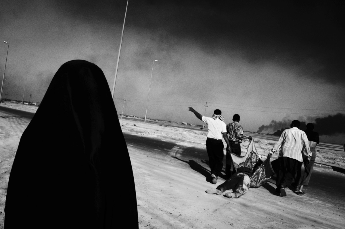 Basra, Iraq, 2003: A group of men drag a dead militant to their vehicle during the British siege of Basra.