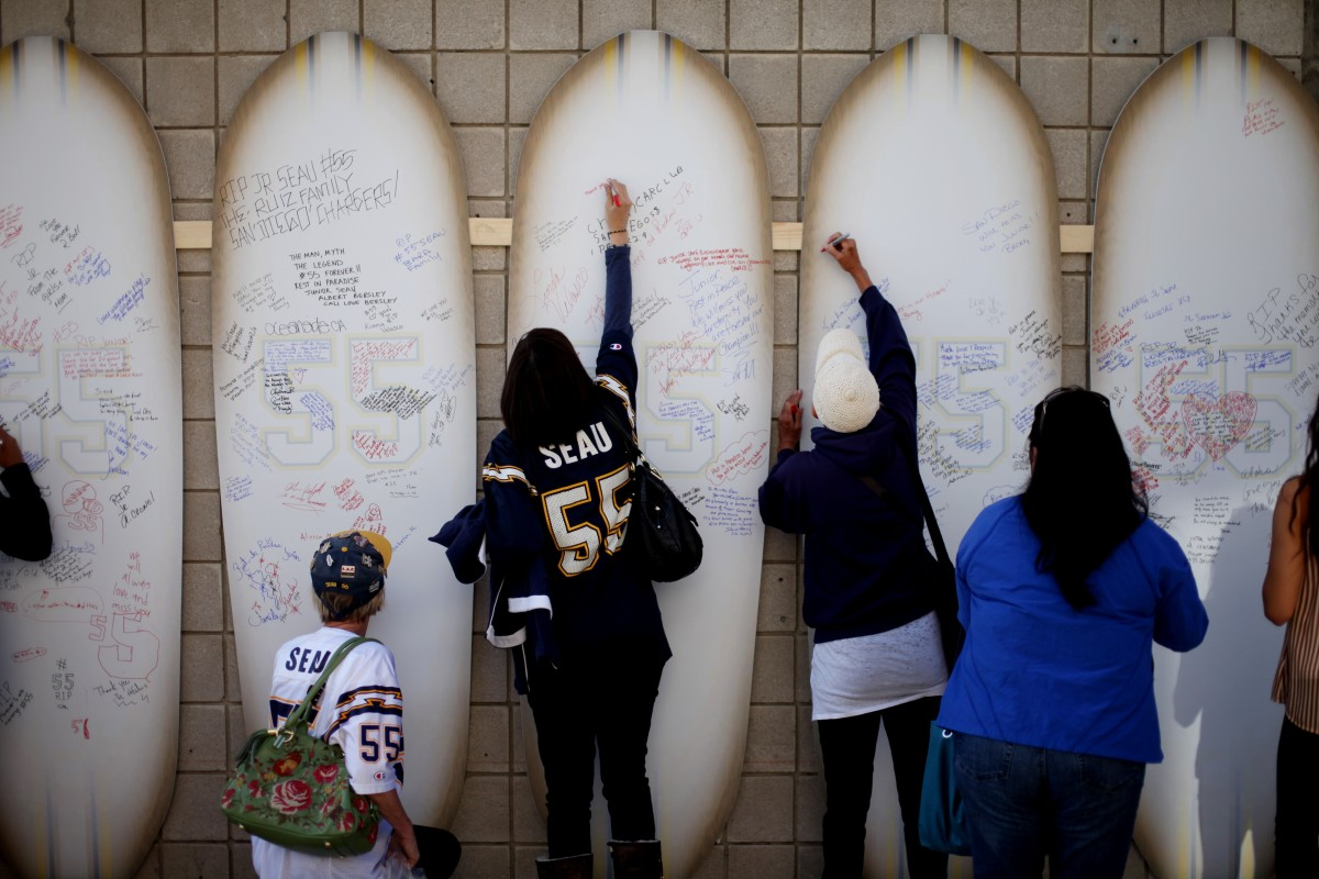 Friends, family members, and supporters sign surfboards as they pay tribute to former NFL star Junior Seau during a public memorial at Qualcomm Stadium on May 11th, 2012, in San Diego, California.