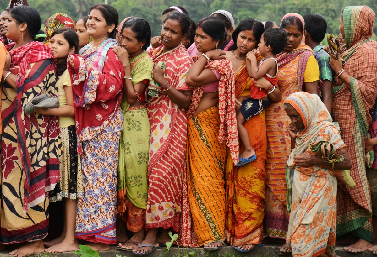 Indian flood victims wait in a queue to collect relief materials in Chitnan village, around 60 km West of Kolkata, on July 28, 2017. The Indian Meteorological Department (IMD) has issued warnings of heavy rains across Gujarat state of Western India in next 24 hours.