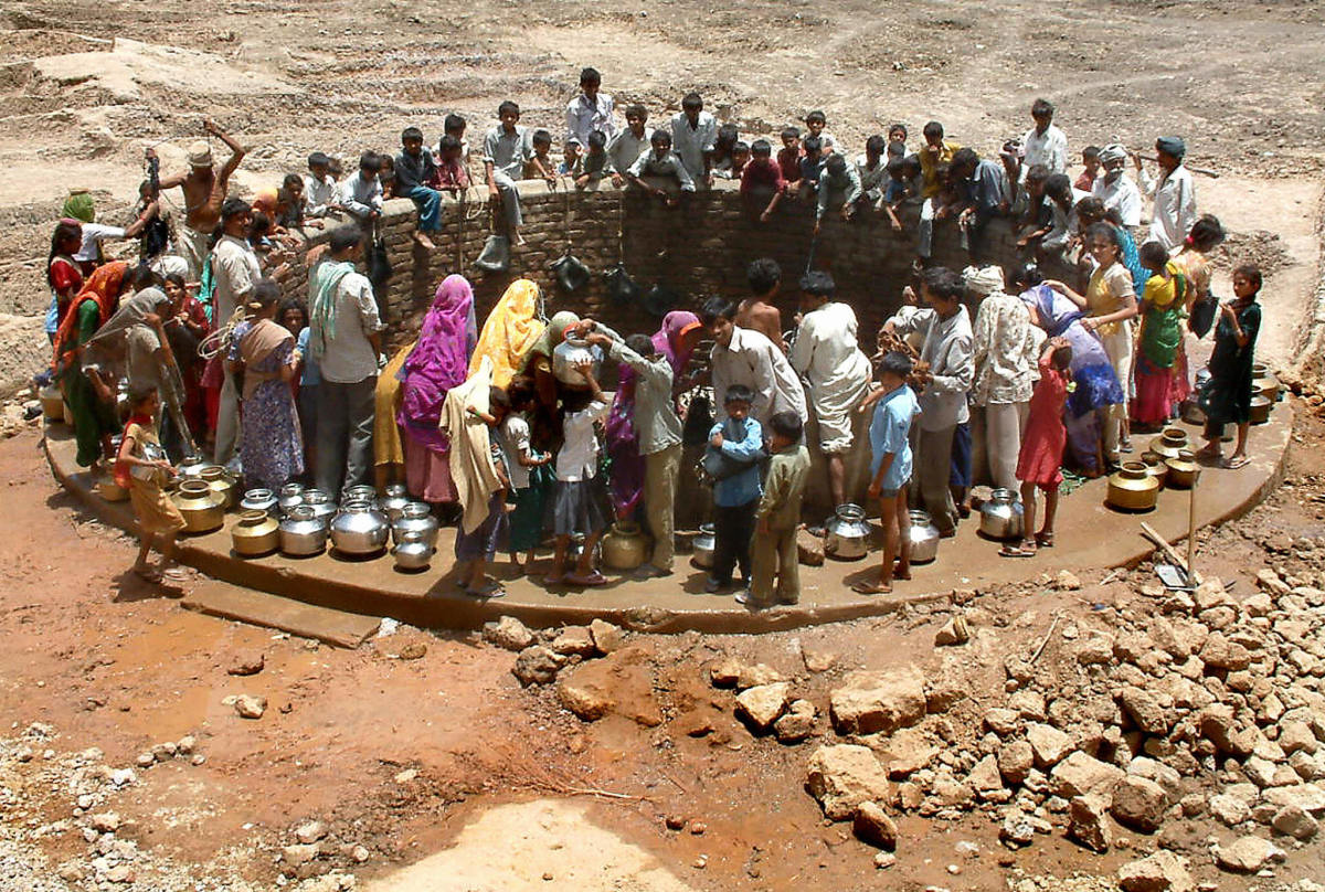 Indian villagers gather around a well to fill their pots with water at Natwargadh village.